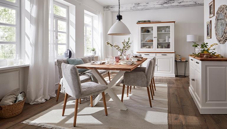 Esszimmer im Landhausstil mit Holztisch und weißen Holzmöbeln mit hellbraunen Akzenten