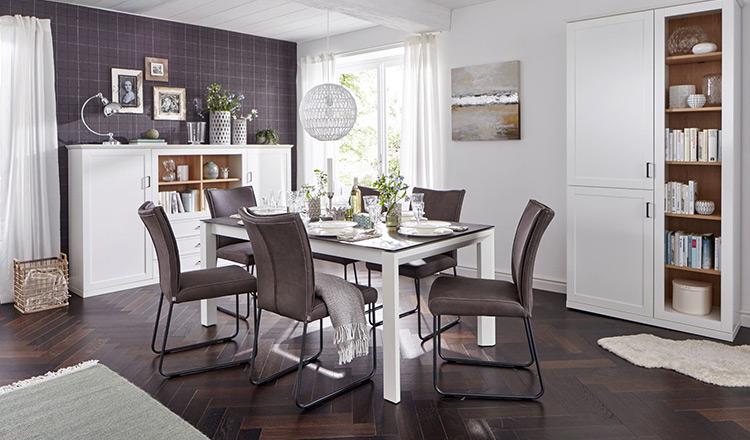 Esstisch im Landhaus-Style umgeben von Stühlen und je einem Side- und Highboard