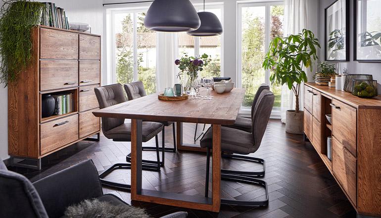 Esszimmer mit Tisch und Highboard aus Massivholz sowie dunkelgrauen Freischwingern