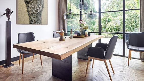 Massivholztisch aus Nussbaum neben schwarzen und modernen Lederstühlen