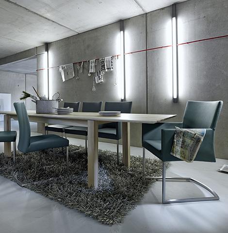 Esszimmer in einem Loft mit Betonwänden, graue Freischwingerstühle vor hellem Massivholztisch