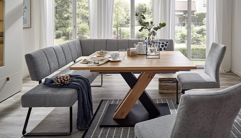 Graue, gepolsterte Eckbank und zwei graue Stühle vor einem Esstisch aus Massivholz