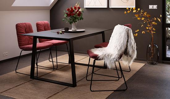 Modern eingerichtetes Esszimmer mit weinroten Kufengestell-Stühlen und einem schwarzen Esszimmertisch mit Kufen