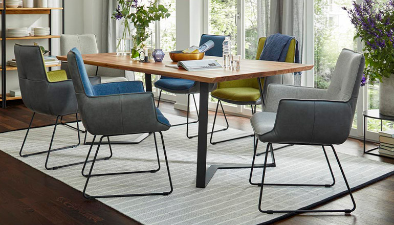 Blaue und grüne Armlehnstühle, die um einen Massivholztisch aufgestellt sind