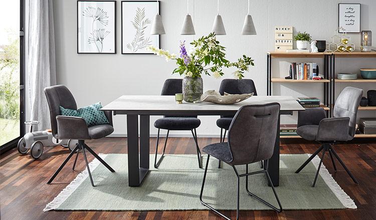 Esstisch mit weißer Platte und modernem Kufengestell umgeben von fünf Stühlen