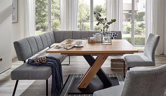 Esstisch aus Holz mit zwei hellgrauen Stühlen und einer hellgrauen Eckbank