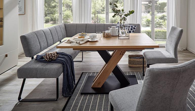 Graue große Eckbank um einen schönen Massivholztisch