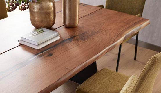 Esstisch aus dunklem Massivholz mit Baumkante dekoriert mit zwei Büchern und zwei Vasen