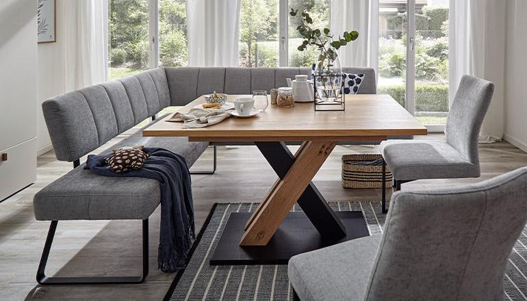 Graue gepolsterte Sitzbank vor einem Esstisch aus Massivholz