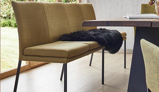 Moderne grüne Sitzbank kombiniert mit schwarzem Fell vor einem hölzernen Esstisch