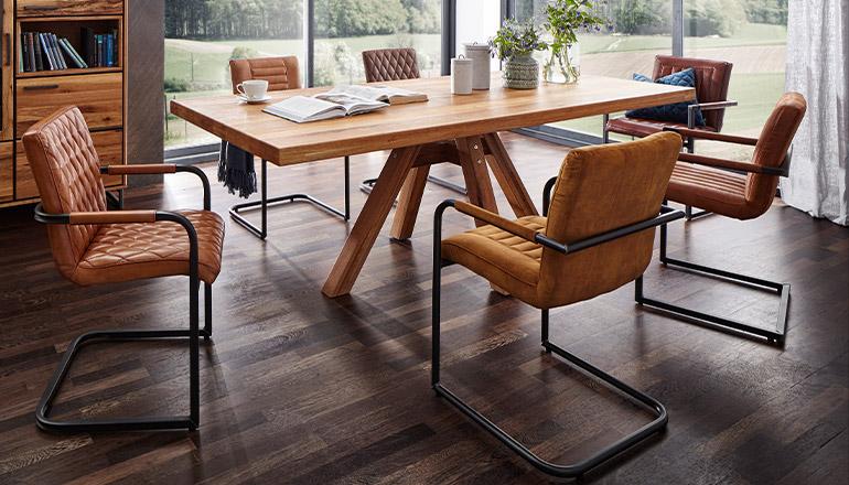 Cogancfarbene Esszimmerstühle mit Armlehnen um einen Esstisch aus Massivholz