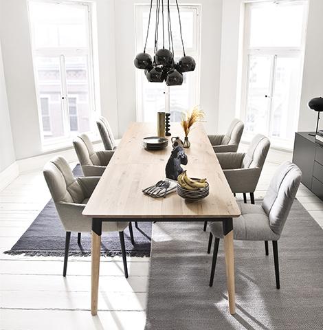 Graue Stühle um einen Esstisch aus Holz im skandinavischen Design