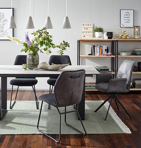 Esszimmerstühle verteilt um einen dekorierten Esstisch mit einem Regal im Hintergrund