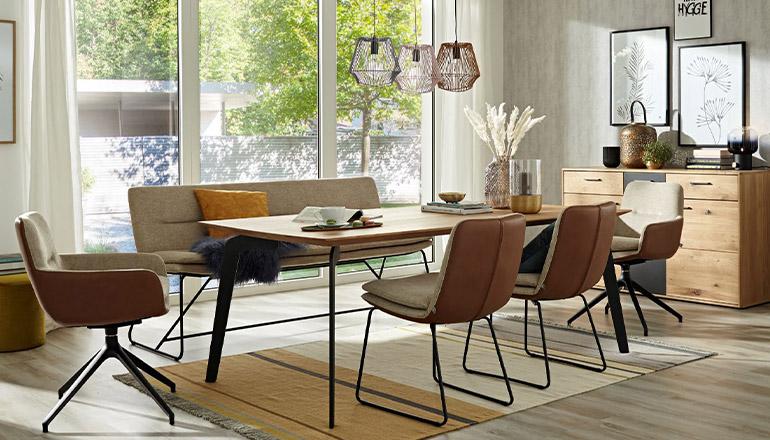 Sitzgruppe aus Stühlen und einer Polsterbank in Braun und Beige Farben um einen Holz-Esstisch