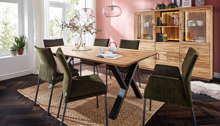 Hellbraune Tischplatte aus Massivholz mit dunkelgrünen Polsterstühlen