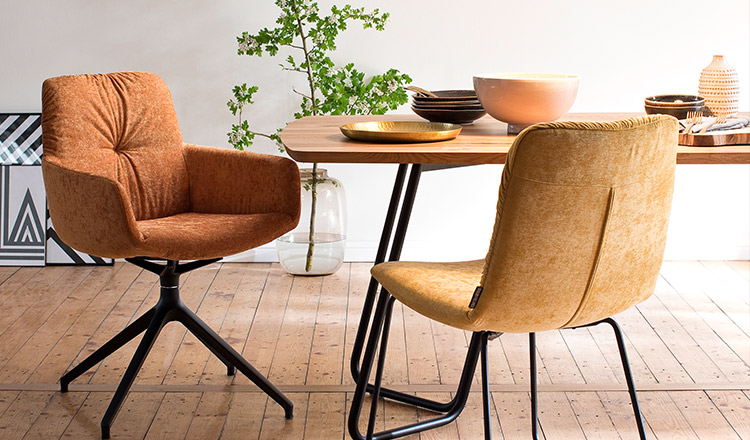 Zwei Stühle mit gelb- und orangefarbenen Stoffbezügen vor einem Esstisch mit Tischplatte aus Massivholz