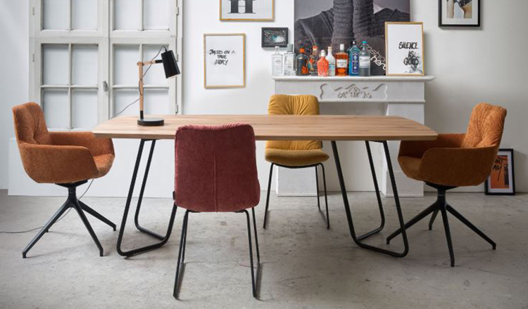 Bunte Stuhl im Retro-Look verteilt um einen Esstisch, ebenfalls im Retro-Style