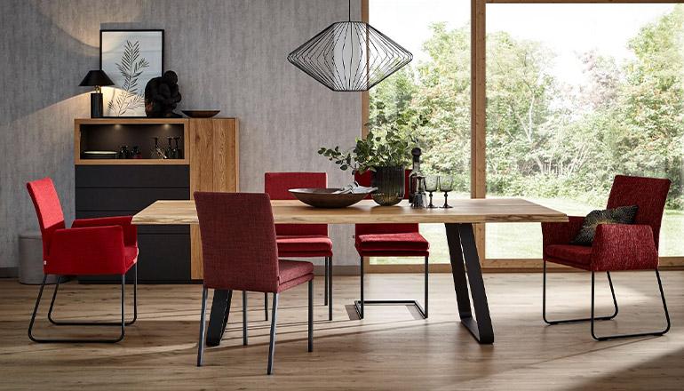 Rote Esszimmerstühle verteilt um einen Esstisch aus Massivholz