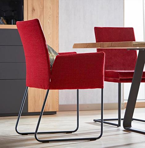 Ein roter Stuhl mit schwarzem Kufengestell neben einem Esstisch aus Massivholz