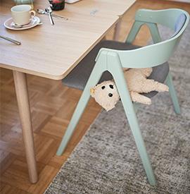 Ein Teddybär auf einem mintfarbigen Stuhl vor einem hölzernen Esstisch im Skandi-Stil