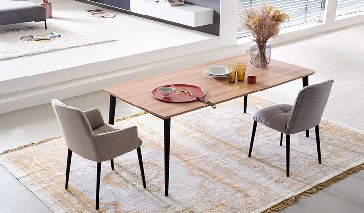 Zwei graue Stühle vor einem Esstisch mit hölzerner Tischplatte im Skandi-Style
