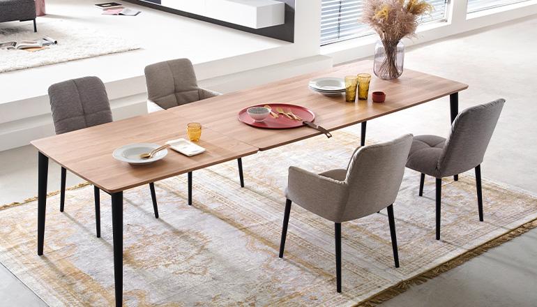 Graue Polsterstühle um einen Esstisch aus Holz mit Deko und Teppich