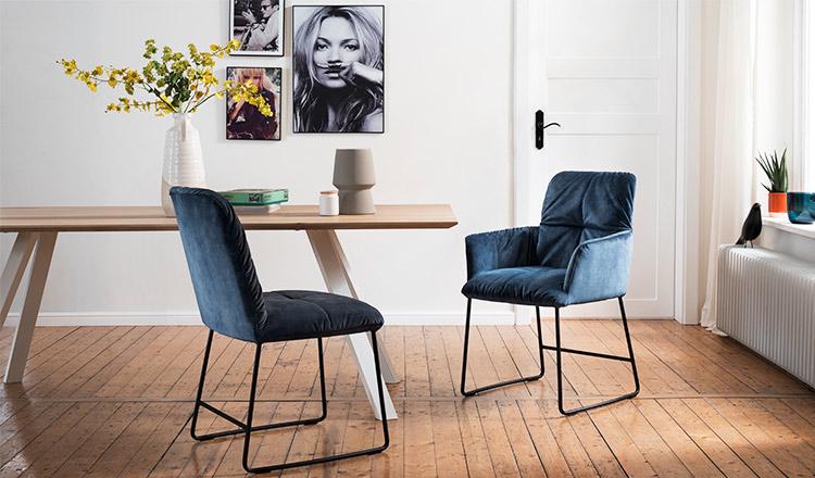 Zwei blaue Esszimmerstühle stehen an einem Esstisch im Skandi-Look