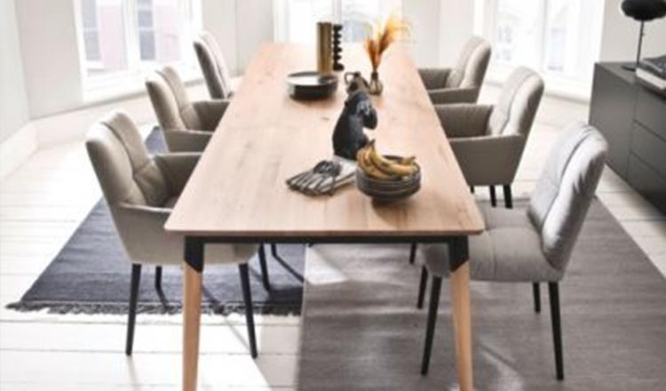Esstisch im Skandi-Style aus Holz umgeben von sechs hellen Stühlen