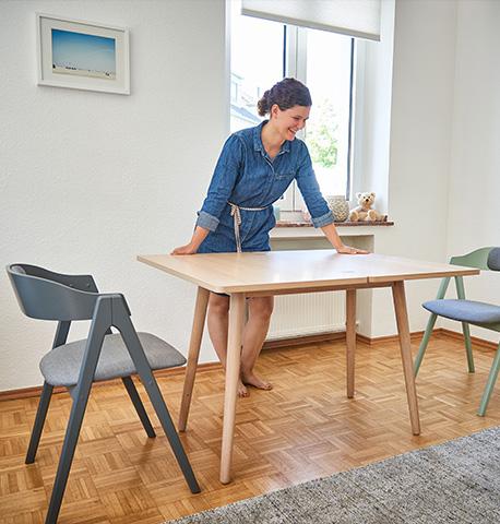Esstisch aus Holz mit schrägabstehenden Füßen und zwei farbigen Stühlen
