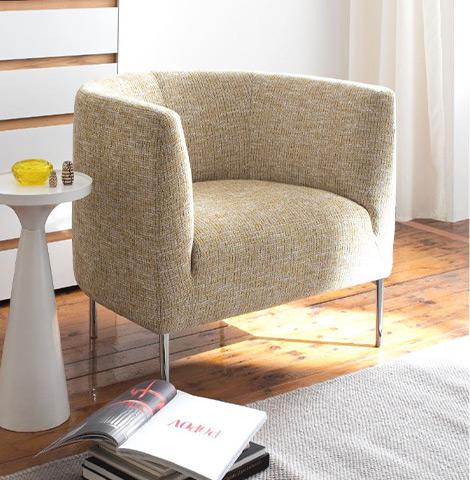 Zitronengelber Sessel vor weiß-brauner Kommode und einem weißen Beistelltisch mit gelber Vase