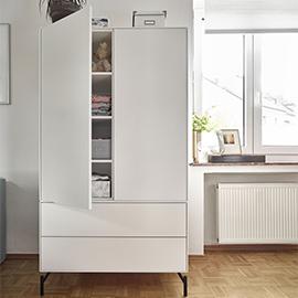 Weißer halb geöffneter Kleiderschrank mit schwarzen Metallfüßen
