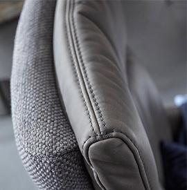 Detailaufnahme einer Rückenlehne aus grauem Stoff und Leder