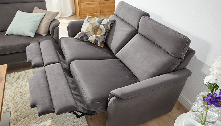 Graues 2-Sitzer Sofa mit aufgebauter Relaxfunktion und einem Deko-Kissen