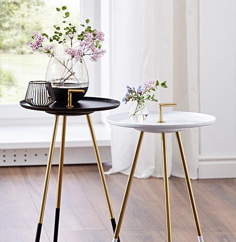 Ein schwarzer und ein weißer runder Beistelltisch mit goldenem Detail auf der Platte