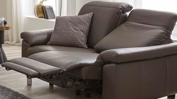 Braune Funktionscouch aus Echtleder mit aufgebauter Relaxfunktion und gemustertem Kissen