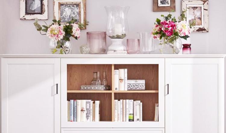 Weißes Highboard geschmückt mit Vasen und Blumensträußen