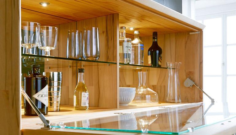 Sideboard mit geöffneter Glasklappe dekoriert mit Flaschen und Gläsern