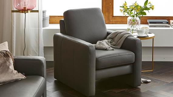 Grauer Loungesessel mit grauer Wohndecke und goldenem Beistelltisch vor einem Fenster