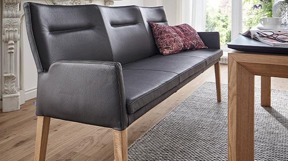 Nahaufnahme einer Sitzbank im dunkelbraunen Echtleder mit Kissen