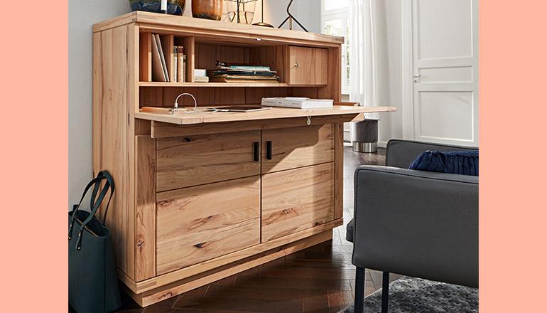Massivholz-Sekretäre mit Buch, davor steht ein Sessel und eine Tasche