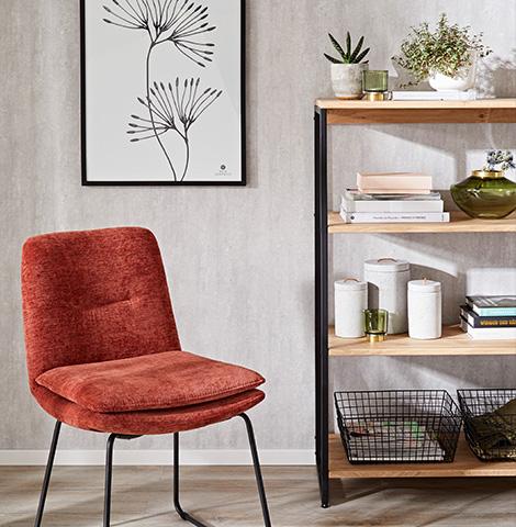 Regal mit hölzernen Einlegeböden und schwarzem Metallgestell neben einem roten Stuhl