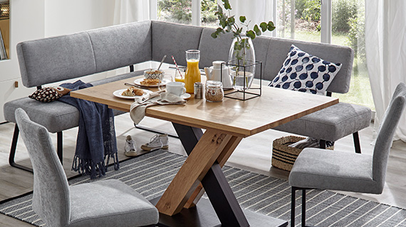Gepolsterte Eckbank in Grau mit zwei anderen Esszimmerstühlen beim Frühstück