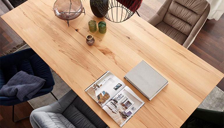 Tischplatte aus hochwertigem Massivholz neben bunten Polsterstühlen