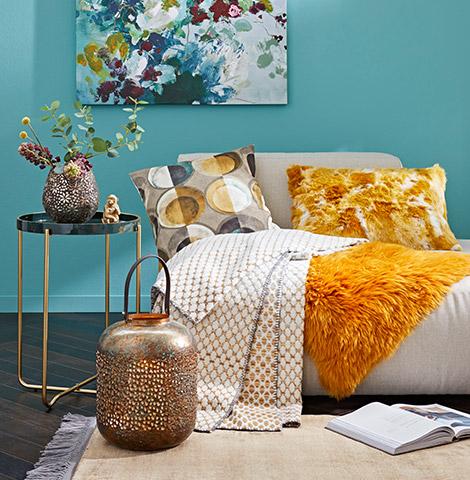 Gelbes Fell und weiß-beige Decke auf Sofa neben Laterne und elegantem Beistelltisch mit einer Vase und Blumen