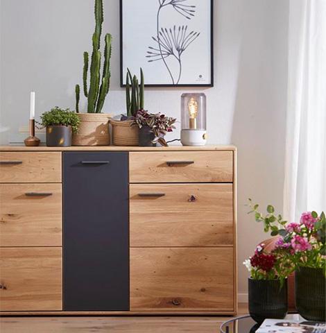 Sideboard aus Massivholz, vor und auf dem viele Pflanzen und Blumen stehen