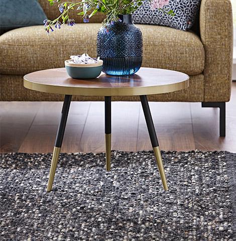 Dunkelgrauer Teppich mit Fransen und kleiner Beitstelltisch aus Holz und Goldfüßen