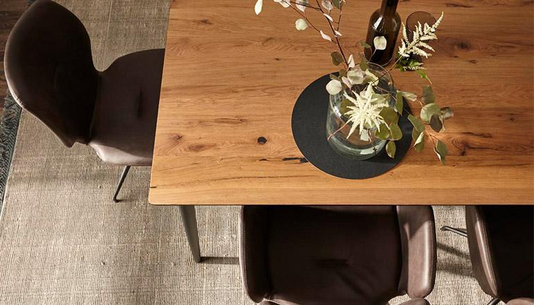 Holztischplatte, auf dem eine Vase mit Blumen steht