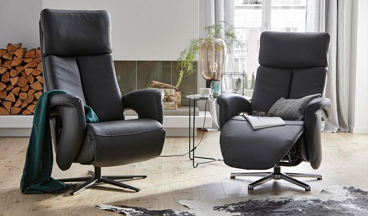 Zwei schwarze Fernsehsessel auf Leder mit einer Relaxfunktion neben einem Beistelltisch