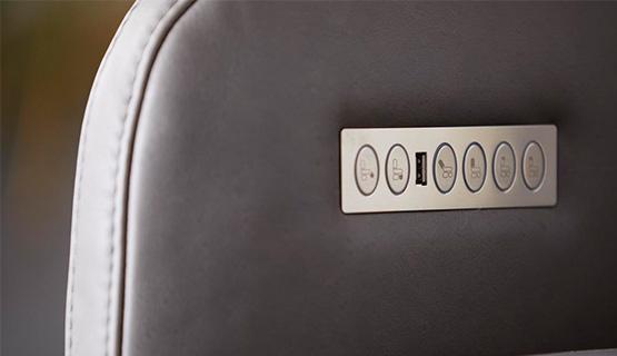 Grauer Ledersessel mit einer silbernen Knopfleiste für die Relaxfunktion
