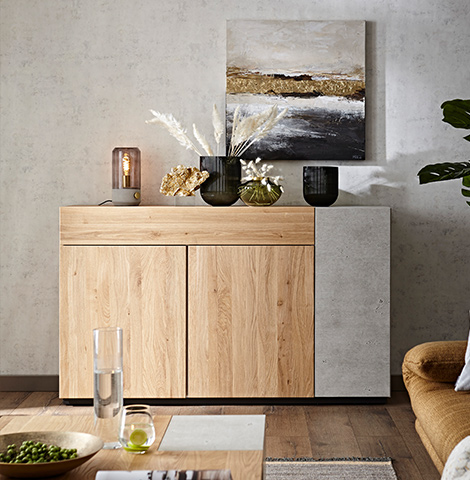 Sideboard aus Massivholz mit einer Front in Beton-Optik hinter einem Couchtisch